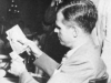 Alger Hiss examines photos of Whittaker Chambers